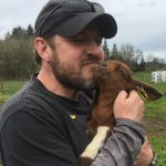 Staff member, Justin Demeter, holding a baby goat at Berggren Demonstration Farm