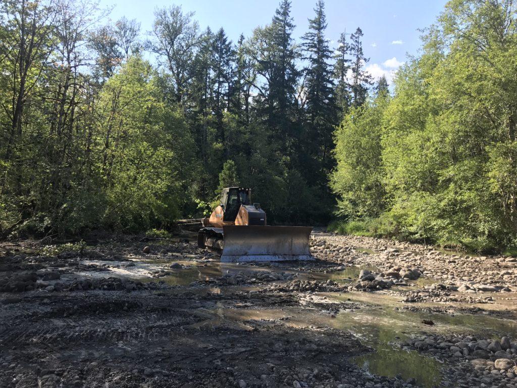 Bulldozer grading dewatered floodplain channel